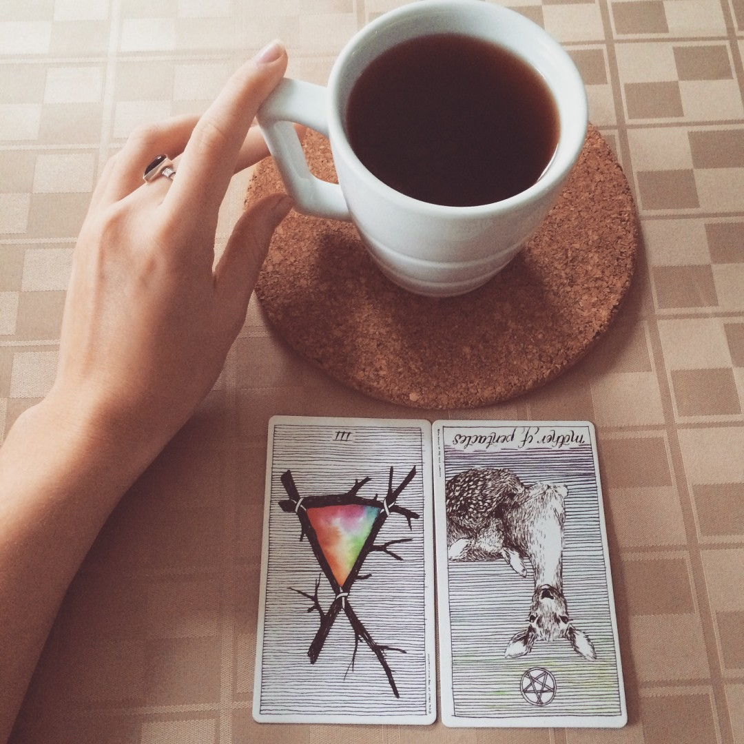 a hand touching a full cup of black tea with the three of wands and the mother of pentacles reversed laid out before the cup