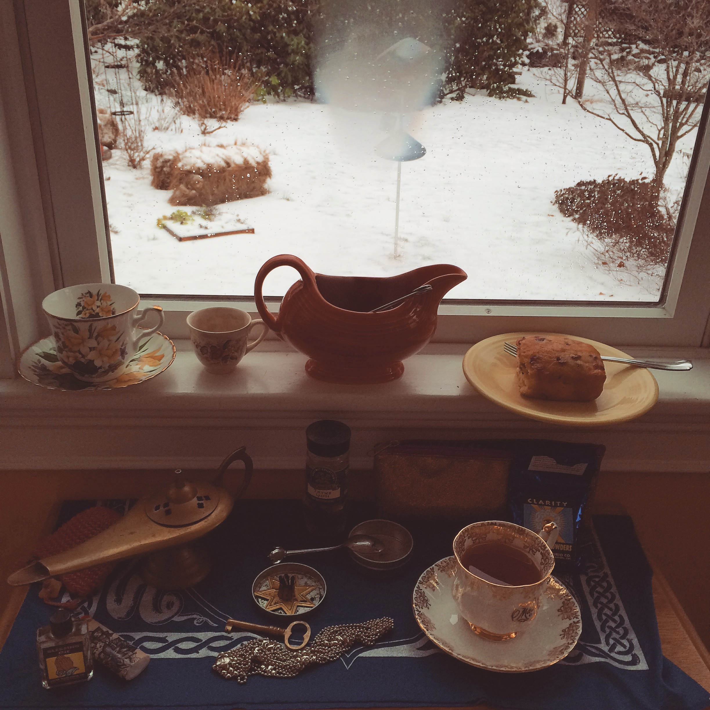 a windowsill altar with makeshift gravy boat teapot, food and drink offerings, and magical curios