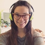 paige smiles and wears lime green headphones and amber eyeglasses