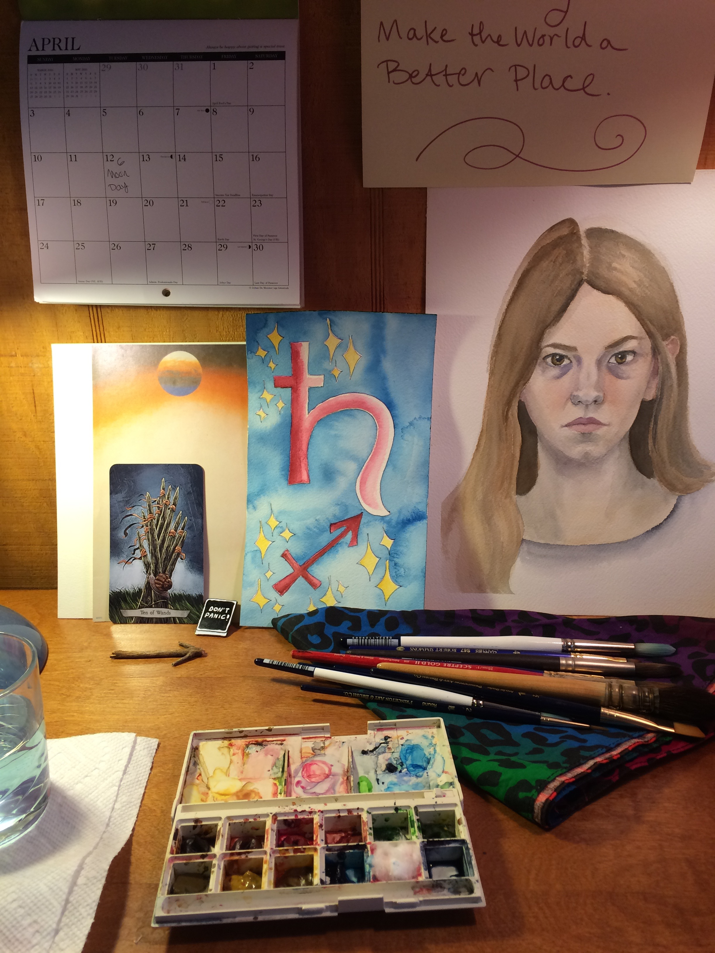 a watercolor palette open on a desk, a group of brushes laying on a rainbow leopard print kerchief beside it. on the wall behind the desk is propped an old unfinished watercolor self-portrait, a watercolor image of the Saturn and Sagittarius sigils on a blue background, a calendar open to April, and the Ten of Wands tarot card leaning against a blank piece of stationary topped with a planet. a glass of painting water is visible on the left.