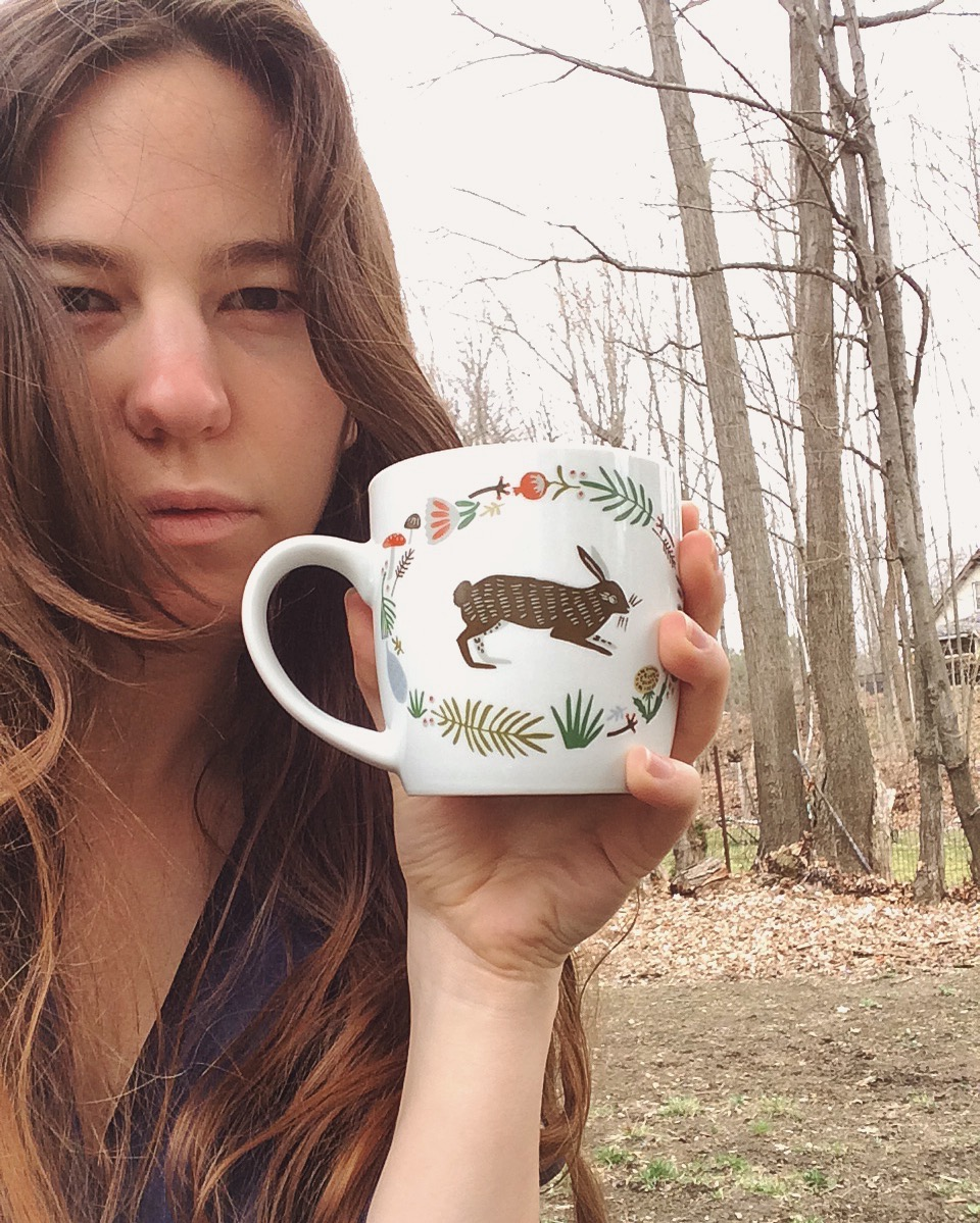 Paige looks at you; bare trees behind steady gaze behind rabbit mug of tea