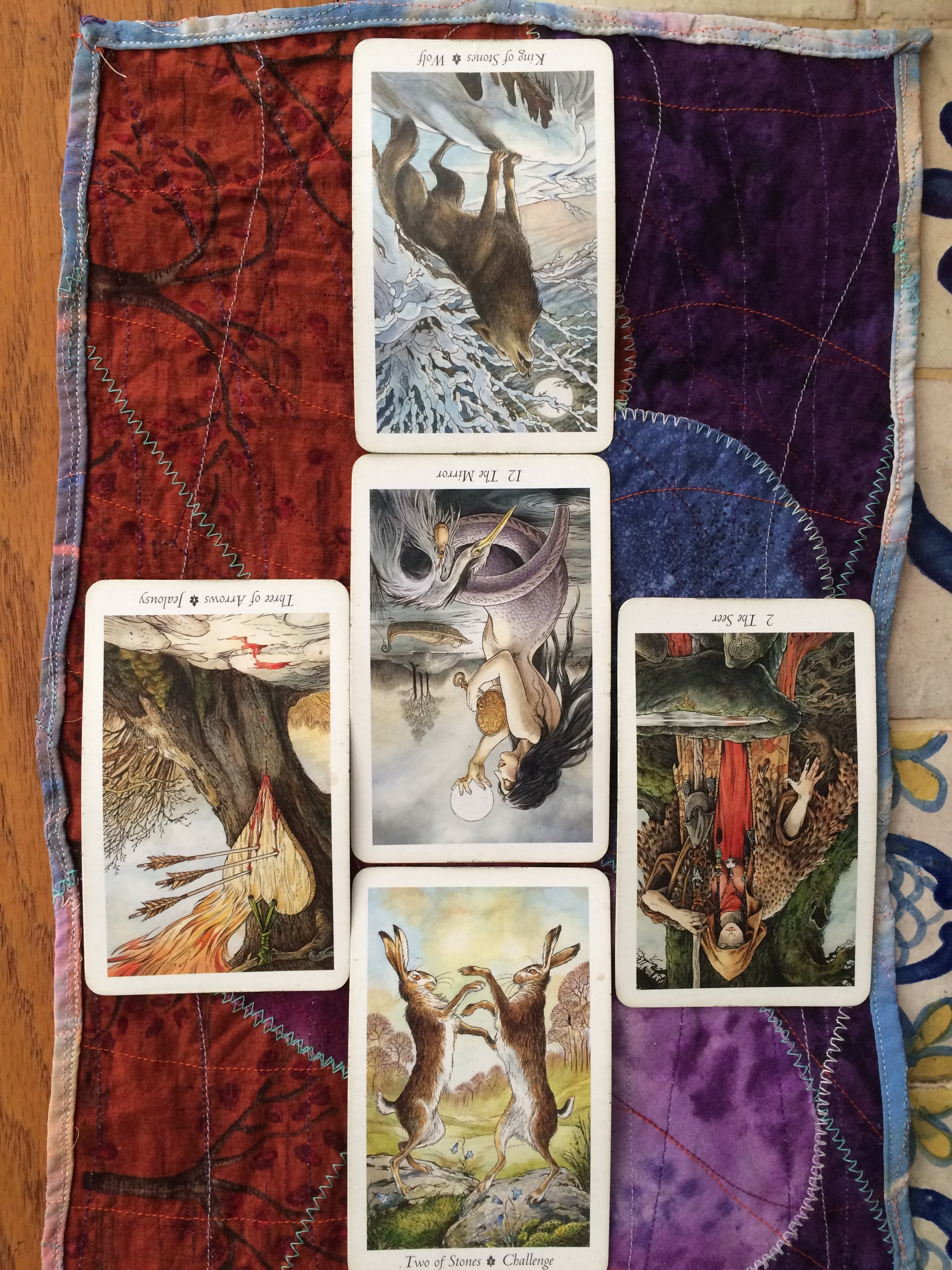 close up of five tarot cards laid out on a purple and red cloth