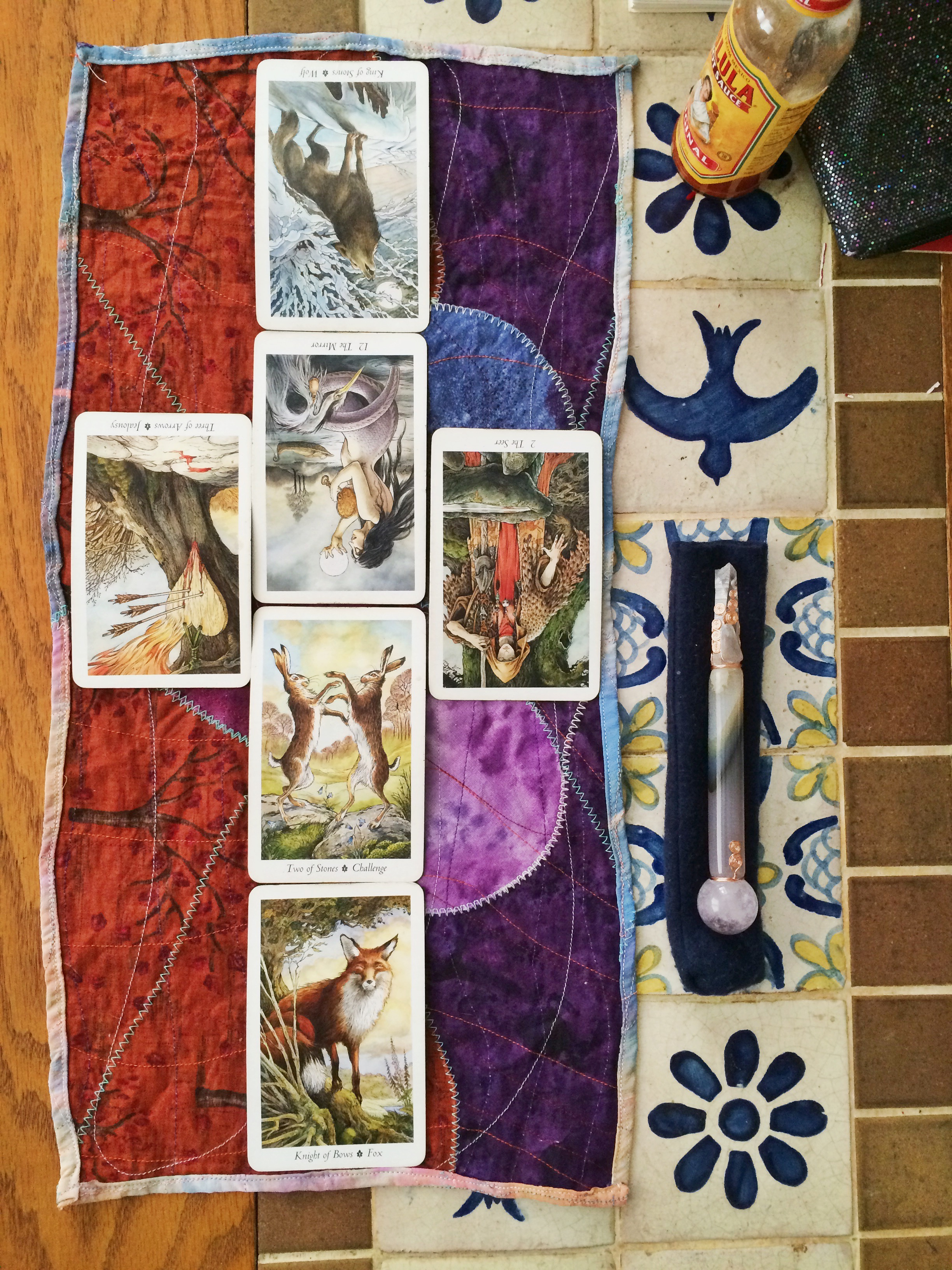 six tarot cards are laid out in a long, skinny cross pattern. to the right is a crystal wand atop a dark blue cloth sheath. beneath it are Mexican tiles of birds and flowers. a bottle of Cholula hot sauce lurks in the background