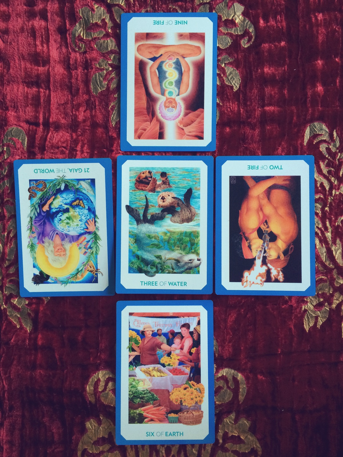 five tarot cards are laid on a red cloth with ornate gold designs upon it