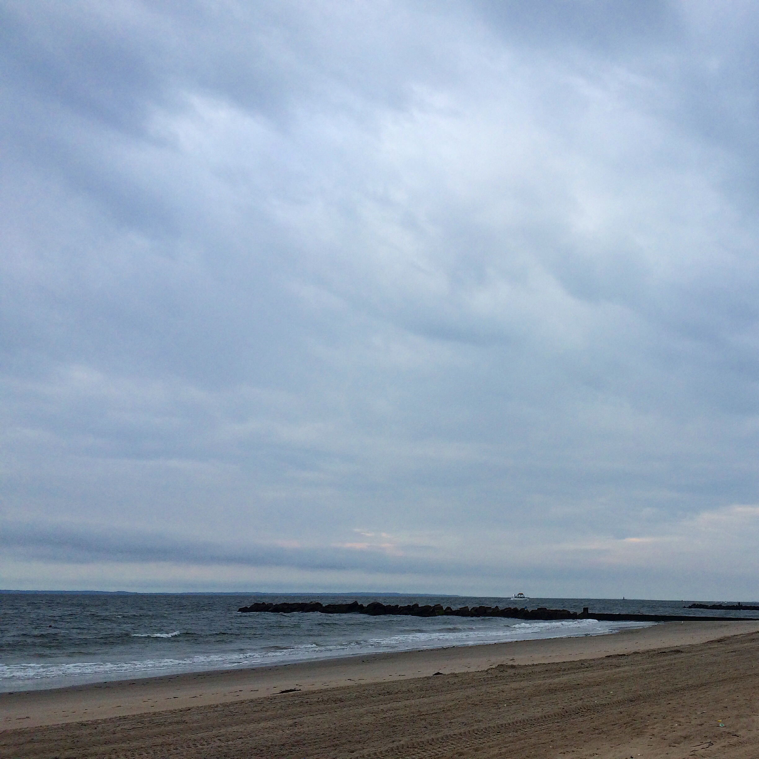 a cloudy morning sky swoops over a small stretch of Brighton Beach