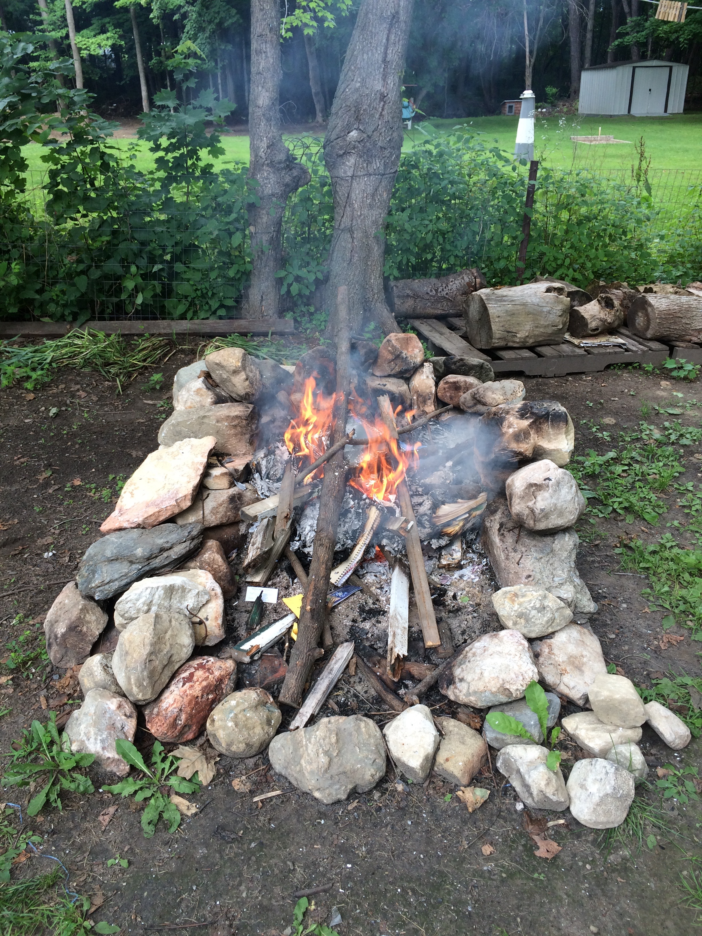 outside. a handmade stone fire pit with a fire burning. white smoke plumes up from the fire, on which are piled old notebooks. in the background, greenery and two tree trunks