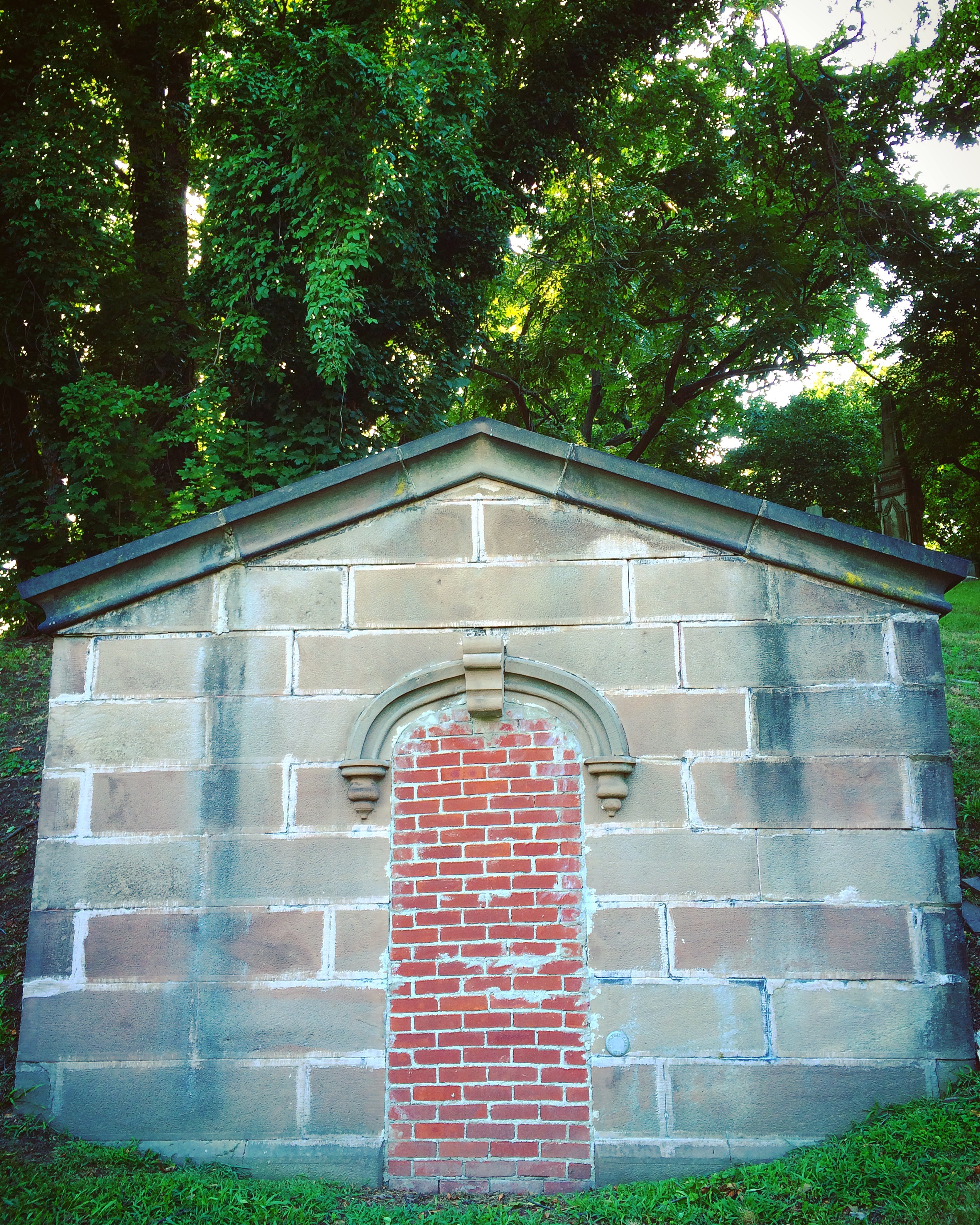 a stone mausoleum with a peaked roof stands before a wall of green trees and overgrowth. its door, beneath a carved arch, is bricked over like some creepy Beetlejuice business