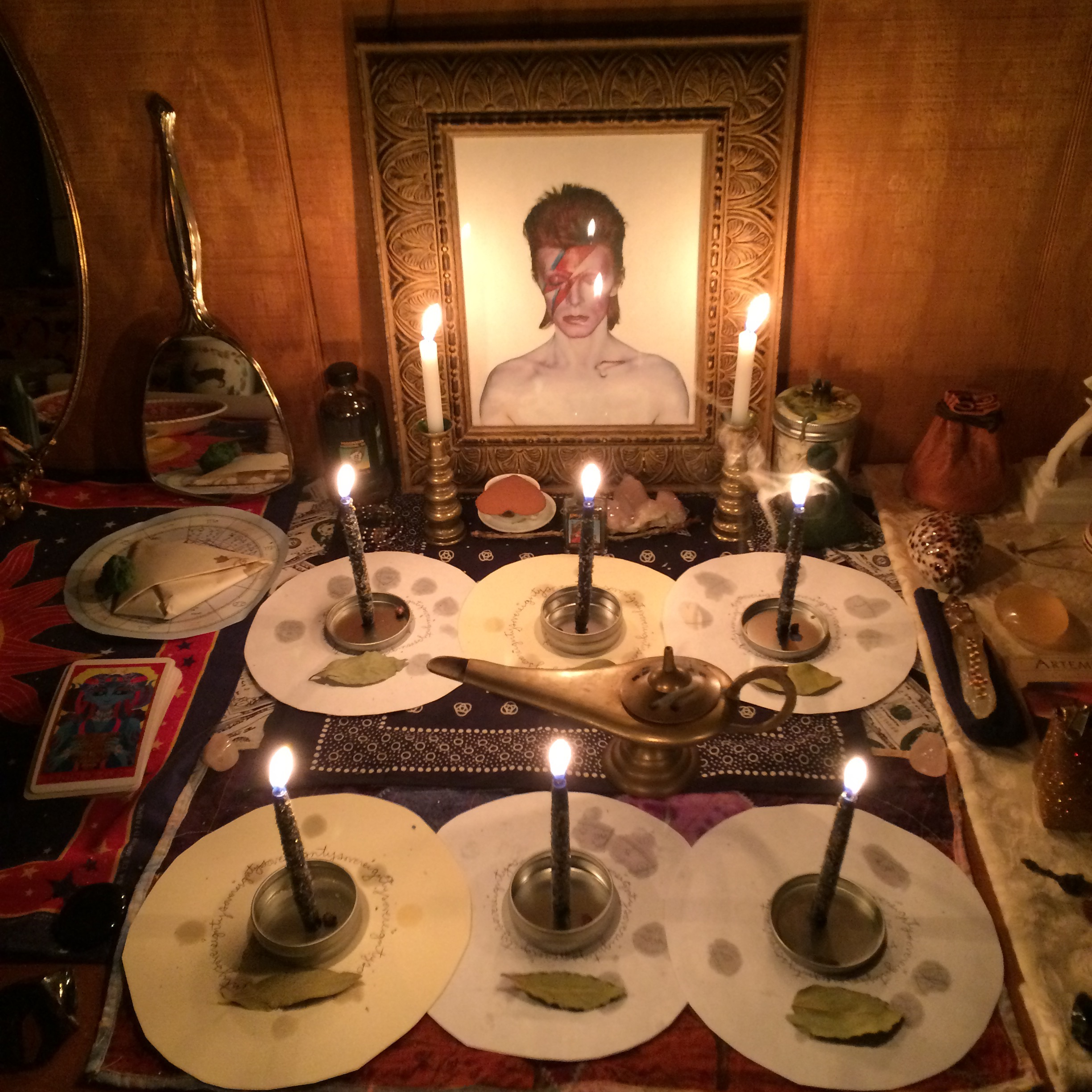 a frame picture of david bowie as aladdin sane with six small candles burning before it each on top of a round paper astrology chart