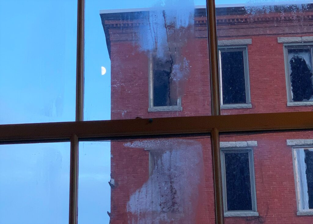 a half moon is visible in the sky next to a brick building with tall thin dark windows, seen through a window fogged with condensation