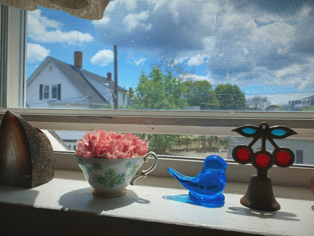 A sunny windowsill with four objects on it. From left to right: a chunky geode rock, a shamrock-pattern teacup holding a spray of cherry blossoms, a glass-blown bluebird of happiness, and a small bell with a stained glass handle in the shape of three cherries. The sky in the background is blue with big puffy white clouds.