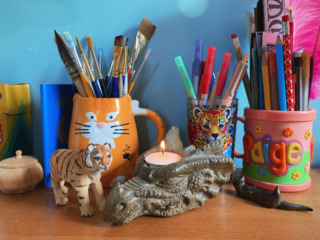A small painted wooden tiger and a stone candle holder shaped like a dragon's head and holding a lit tealight. Behind the figurines are three cups filled with paintbrushes, pens, and pencils. The left cup is shaped like an orange cat, the middle cup has a Lisa Frank rainbow leopard on it, and the third cup says PAIGE in multicolored letters.