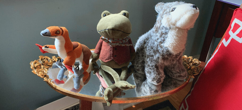 Three stuffed animals sitting on an oval mirror. From left to right: An orange dinosaur-bird, the Jellycat Riverside Rambler frog wearing an oxblood vest and striped scarf, and a grey wolf resting on her haunches. The mirror is rimmed in gold and has one handle on either side. Each handle is fashioned like a bunch of roses.